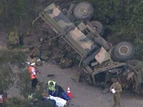 Photographs and video footage of the accident show the truck lying on its side, next to an embankment with military backpacks and other equipment spilling out. (ninemsn.com.au)
