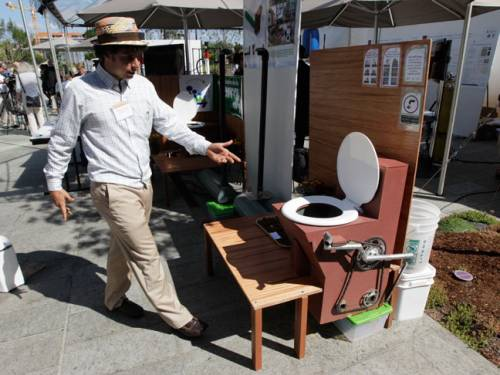 A competitor shows his invention at the 'Reinvent the Toilet Fair'. (Getty)