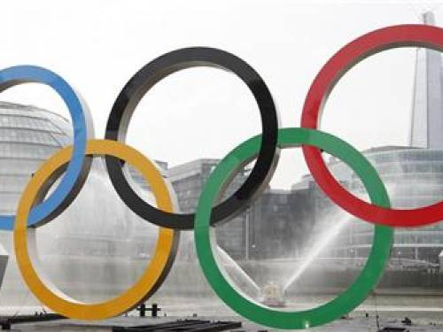 Olympic rings, mounted on a barge, are positioned in front of County Hall and the Shard during a promotional event for the London 2012 Olympic Games, on the River Thames in London February 28, 2012. REUTERS/Andrew Winning