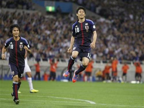 Japan's Shinji Kagawa (r) jumps to celebrate his goal against Jordan at the 2014 World Cup qualifying soccer match in Saitama, north of Tokyo. (Reuters)