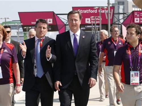 Britain's Prime Minister David Cameron (C) walks with Chairman of the Olympic Organising Committee (LOCOG) Sebastian Coe (2nd L) at the Olympic Park in Stratford in east London July 26, 2012. REUTERS/Suzanne Plunkett