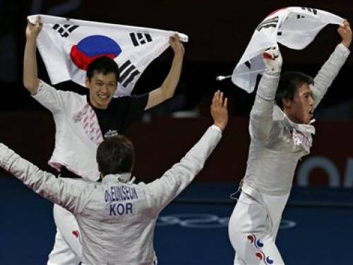 (L-R) South Korea's Bongil Gu, Eunseok Oh and Woo Young Won celebrate with their national flag winning at the end of their men's sabre team gold medal fencing competition against Romania at the ExCel venue at the London 2012 Olympic Games August 3, 2012. REUTERS/Mike Hutchings