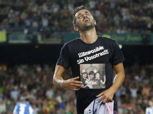 Barcelona's David Villa celebrates his goal against Real Sociedad by wearing a T-shirt with a picture of his family, which reads: