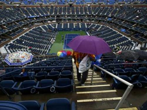 Tennis fans shelter under umbrellas in the rain at the U.S. Open tennis tournament in New York, September 5, 2012. REUTERS/Eduardo Munoz