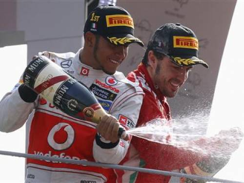 McLaren Formula One driver Lewis Hamilton (L) of Britain sprays champagne on the podium with third placed Ferrari Formula One driver Fernando Alonso of Spain, after winning the Italian F1 Grand Prix at the Monza circuit September 9, 2012. REUTERS/Stefano Rellandini