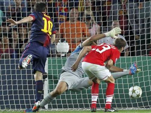 Barcelona's Lionel Messi (L) scores his second goal against Spartak Moscow's Dmitri Kombarov (R) and goalkeeper Andriy Dykan during their Champions League Group G match at Nou Camp stadium in Barcelona, September 19, 2012. REUTERS/Albert Gea
