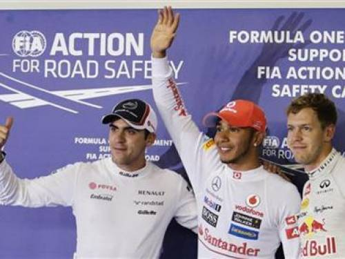 Williams Formula One driver Pastor Maldonado of Venezuela (L), McLaren Formula One driver Lewis Hamilton of Britain and Red Bull Formula One driver Sebastian Vettel of Germany (R) celebrate after the qualifying session of the Singapore F1 Grand Prix at the Marina Bay Street Circuit in Singapore September 22, 2012. Hamilton took the pole position while Maldonado placed second and Vettel, third. REUTERS/Tim Chong