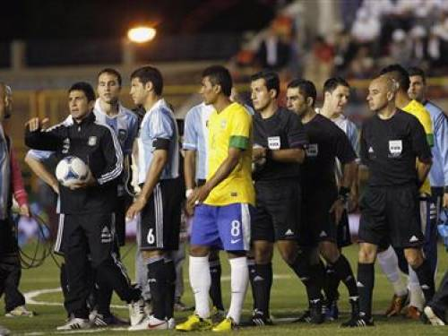 Argentina's players, Brazil's Paulinho (C, front) and referee Enrique Osses (C, in black) from Chile wait for the lights to be restored during a partial blackout before their friendly soccer match in Resistencia, Chaco province, October 3, 2012. REUTERS/Marcos Brindicci