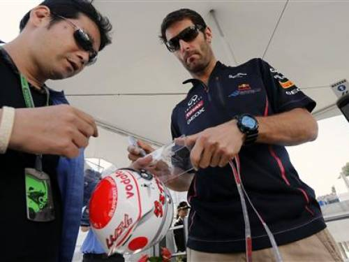 Red Bull Formula One driver Mark Webber (R) of Australia signs autographs before the Japanese F1 Grand Prix. (Reuters)