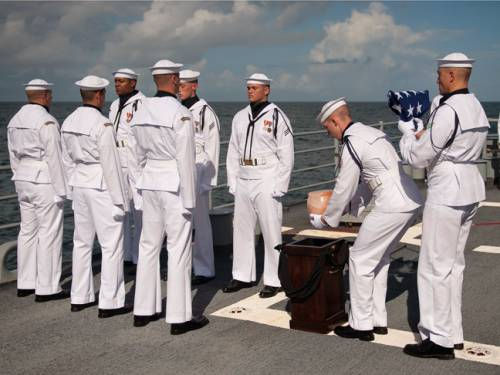 US Navy personnel carry the remains of Apollo 11 astronaut Neil Armstrong during a burial at sea service. (AAP)