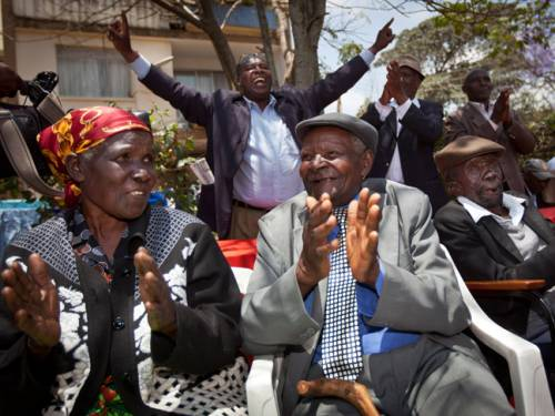Kenyans Jane Muthoni Mara (l), Wambuga Wa Nyingi, and Paulo Muoka Nzili, celebrate the announcement of a legal decision in their case at Britain's High Court concerning Mau Mau veterans. (AAP)