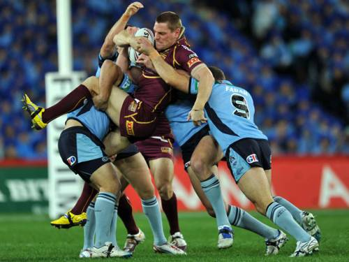 Queensland's Brent Tate is tackled by Greg Bird, Mitchell Pearce and Robbie Farrah of New South Wales. (AAP)