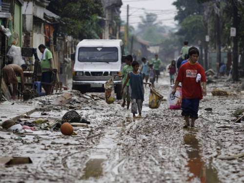 Filipinos walk along a muddy road after floods recede in suburban Marikina city, east of Manila, Philippines. (AAP)