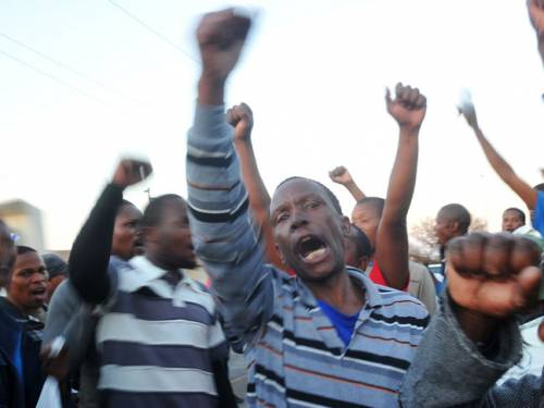 The freed workers sang and danced as they left the court while 10 minibuses readied to take them back to Marikana. (Getty)