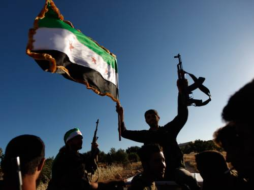 A Free Syrian Army member holds a weapon and a Syrian revolutionary flag during a training session on the outskirts of Idlib, Syria. (AAP)