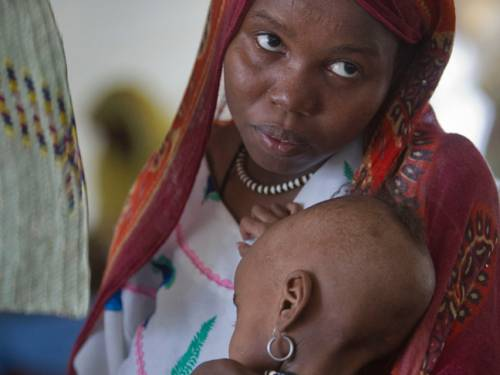 A child, suffering from malnutrition, is held by her mother in an intensive care tent in the desert village of N'Gouri in the Sahel region of Africa. (AAP)