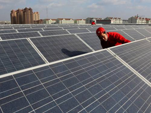 A worker checks arrays of solar panels on the rooftop of a building. (AAP)