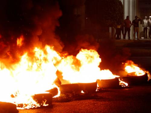 Burning tires block a road next to a clothing store during a protest after a deadly car bomb attack targeting Wissam al-Hassan, the intelligence chief of Lebanon's domestic security forces. (AAP)
