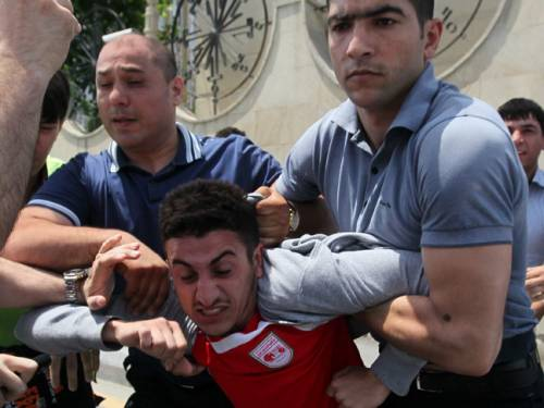 An opposition supporter is detained by Azerbaijani police officers. (AAP)