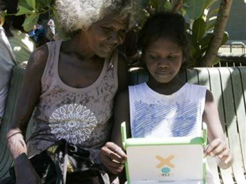 An Australian aboriginal school child works on a laptop computer as part of the