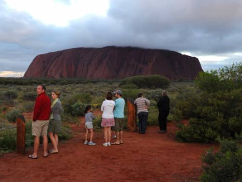 Tourists gather at the sunset carpark at Uluru on sunset ahead of celebrations for the 25th anniversary of the handback of Uluru to its traditional owners (AAP)