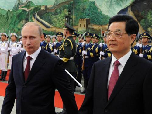 Chinese President Hu Jintao and Russian President Vladimir Putin walk after reviewing an honour guard during a welcoming ceremony at the Great Hall of the People in Beijing. (Getty Images)