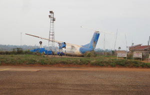 Kigoma airport - one that didn't make it. I was told this was a successful crash because no lives were lost. An airport worker told me the wreck remains not as a testament to safety, but because it was too costly to remove. The terminal is at the right. (SBS)