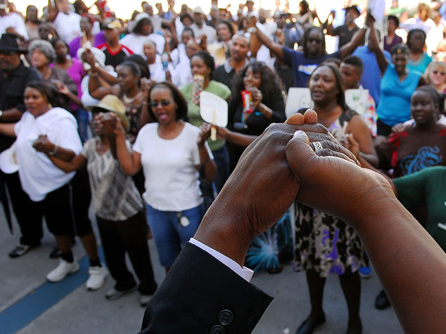A senior pastor at St. James AME Church leads people in a prayer at the Titusville Courthouse in Florida. (AAP)