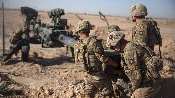 US troops manoeuvring a howitzer in Afghanistan