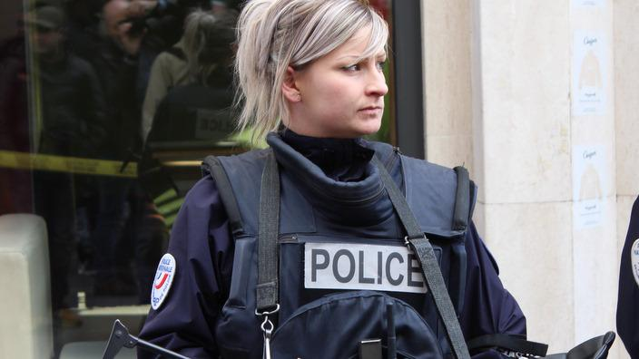 A police officer patrols near the site where police raided an apartment containing suspected terrorists in Paris