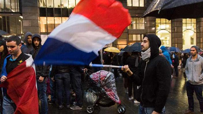 A Sydney resident waves the French flag at a vigil in Martin Place on November 14, 2015