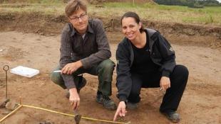 Søren M. Sindbæk og Nanna Holm viser resterne af de brændte planker ved den ene borgport.