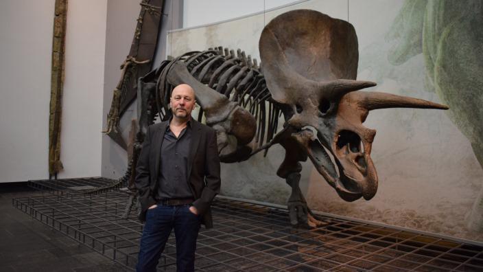 Leiter Dr. Bernd Herkner vor dem 18 Meter langen Dinosaurierskelett im Eingangsbereich