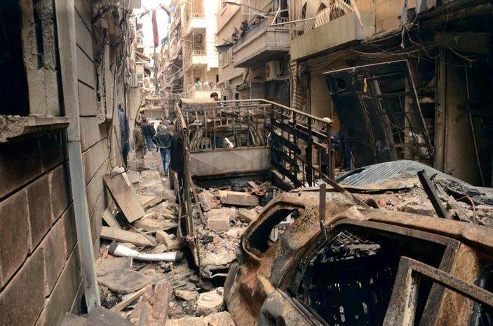 Siriani in una strada cokpita dai bombardamenti