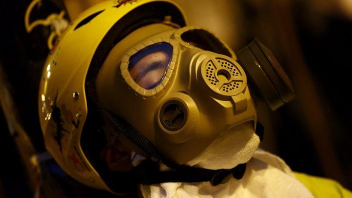 Hong Kong protester rests in a gas mask