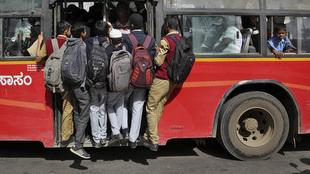 Indian students hang on the door of a crowded bus on their way to school during morning rush hour in Bangalore - AAP
