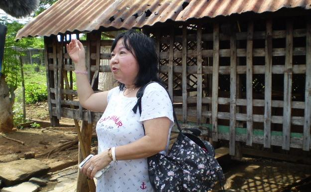 Former refugee Kim Huong infront of a house in Palawan camp