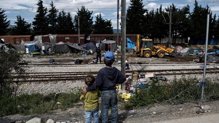 Children watch as a bulldozer removes tents from the train tracks at Idomeni refugee camp, Greece