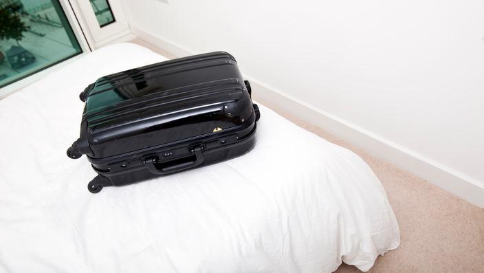 Black suitcase on bed